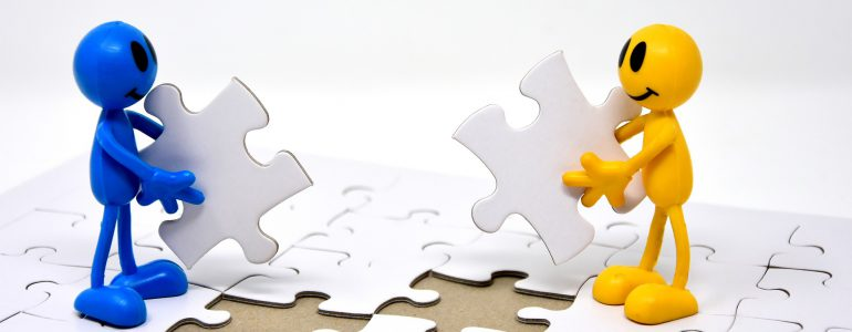 two people putting together puzzle pieces
